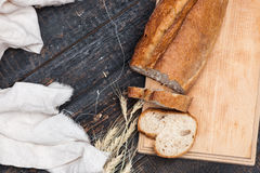 Rustic bread on wood table. Dark woody background with free text space. The macro view of rustic bread on an old vintage wooden table. Dark woody background royalty free stock photo