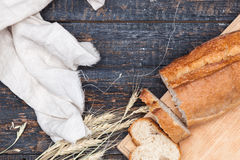 Rustic bread on wood table. Dark woody background with free text space. The macro view of rustic bread on an old vintage wooden table. Dark woody background royalty free stock image