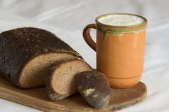 Rustic breakfast. Brown rye bread with a mug of sour milk Royalty Free Stock Photography