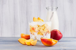 Rustic breakfast with corn flakes, slice peach and milk bottle on white wood board. Royalty Free Stock Images