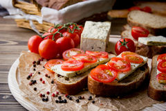 Rustic breakfast with homemade bread, branch of tomatoes, tofu and pepper on the round wooden desk. Country breakfast concept Royalty Free Stock Photos