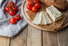 Rustic breakfast with homemade bread, branch of tomatoes, tofu and pepper on the round wooden desk. Country breakfast concept Stock Photography