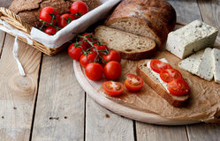 Rustic breakfast with homemade bread, branch of tomatoes, tofu and pepper on the round wooden desk. Country breakfast concept Stock Images