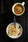 Rustic Breakfast with muesli and cup of coffee on old dark woode Stock Images