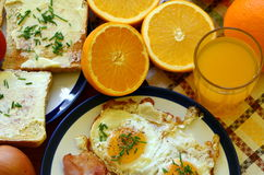 Rustic breakfast - roasted bread with butter and chives, fried eggs and bacon Royalty Free Stock Image