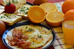 Rustic breakfast - roasted bread with butter and chives, fried eggs and bacon. Royalty Free Stock Photo