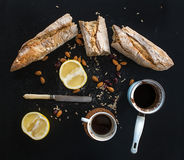 Rustic breakfast set of french baguette broken into pieces, grapefruit, sunflower seeds, almonds and coffee on dark. Rustic breakfast set of french baguette Royalty Free Stock Photos