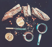 Rustic breakfast set of french baguette broken into pieces, grapefruit, sunflower seeds, almonds and coffee on dark Royalty Free Stock Photos