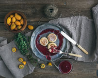 Rustic breakfast set. Russian cheese cakes on a vintage metal plate with lingonberry jam, fresh kumquats, thyme, decoration rope a Royalty Free Stock Photo
