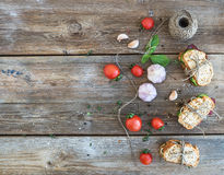 Rustic breakfast set. Sandwiches with smoked meat, cherry-tomatoes, cucumbers, garlic, thyme and basil on rough wood background Royalty Free Stock Images