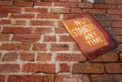 Rustic brick No Standing any time sign stock photography