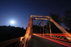 Rustic Bridge. A car streaks by as the moon rises in this seven minute time exposure Royalty Free Stock Photo