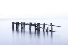 Rustic broken pier wooden posts standing in calm blue lake water Stock Photos