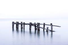 Free Rustic Broken Pier Wooden Posts Standing In Calm Blue Lake Water Stock Photos - 89099723