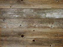 Rustic brown weathered barn wood board background. Rustic brown with grey weathered barn wood board background showing rich grain and knots Royalty Free Stock Photo