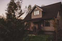 Rustic brown wooden country house in autumn evening. Brown wooden country house in autumn evening Royalty Free Stock Photo