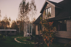 Rustic brown wooden country house in autumn evening. Brown wooden country house in autumn evening Royalty Free Stock Photos