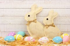 Burlap Easter Bunnies with eggs in straw against white wood. Rustic burlap Easter Bunnies with surrounding eggs in straw. e view with a white wood background Stock Photos