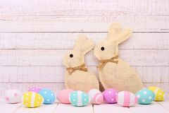 Burlap Easter Bunnies with eggs against white wood. Rustic burlap Easter Bunnies with surrounding pastel eggs. Side view with a white wood background Stock Photos