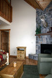 Rustic cabin. The interior of a rustic cabin showing a stone fireplace, lots of wood and a stag's head mounted over the mantle royalty free stock photography