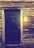 Rustic cabin door with porch light. Old rustic vintage antique house home building structure with green intricate front door and porch light lantern glowing Royalty Free Stock Photo