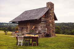 Rustic Cabin Fall Outdoor Dinner Party. A fall outdoor dinner party set up in front of a Rustic log cabin. The dinner table is set up on an antique dining room Royalty Free Stock Photography