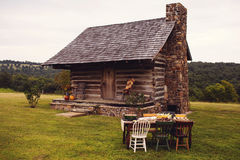 Rustic Cabin Fall Outdoor Dinner Party. A fall outdoor dinner party set up in front of a Rustic log cabin. The dinner table is set up on an antique dining room Royalty Free Stock Photos