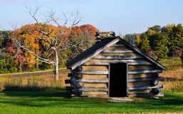 Rustic cabin in field. Rustic wooden cabin in green field with autumn foliage on sunny day Stock Photo