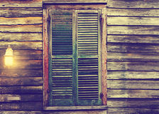 Rustic cabin window with closed shutters and porch light Stock Photography