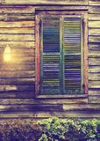 Rustic cabin window with closed shutters and porch light Royalty Free Stock Images