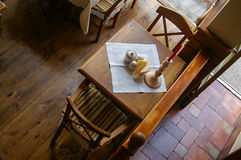 Rustic cafe table for two. Overhead view of a rustic wooden cafe table for two, set with white linen, condiment set and a candlestick royalty free stock image