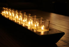 Rustic Candles on Wooden Table. A row of romantic white candles light a dark rustic wooden table Stock Photography