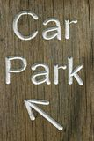 Rustic car park directional sign with arrow. Rustic car park directional sign routed into well grained wood and with white letters spelling the words car park Stock Photography
