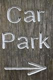 Rustic car park directional sign with arrow. Rustic car park directional sign routed into well grained wood and with white letters spelling the words car park Stock Images