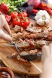 rustic A carne de porco suculenta é cortada com uma faca e uma forquilha No espeto apetitosos e legumes frescos em um fundo de ma Foto de Stock Royalty Free