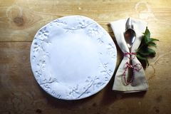 Rustic casual country dinner place setting with hand made plate for Thanksgiving or Christmas. Horizontal aspect Stock Photos