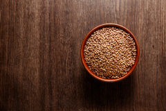 Rustic ceramic bowl of uncooked lentils on dark wood. Rustic ceramic bowl of uncooked lentils  on dark wood from above Royalty Free Stock Image