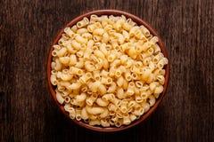 Rustic ceramic bowl of uncooked pasta spaghetti on dark wood. Rustic ceramic bowl of uncooked pasta spaghetti  on dark wood from above Stock Image
