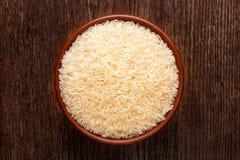 Rustic ceramic bowl of uncooked raw basmati rice on dark wood. Rustic ceramic bowl of uncooked raw basmati rice  on dark wood from above Royalty Free Stock Image