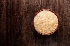 Rustic ceramic bowl of uncooked raw basmati rice on dark wood. Rustic ceramic bowl of uncooked raw basmati rice  on dark wood from above Stock Photos