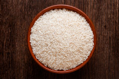 Rustic ceramic bowl of uncooked raw white rice on dark wood. Rustic ceramic bowl of uncooked raw white rice  on dark wood from above Royalty Free Stock Photography