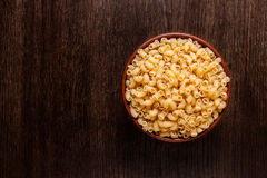 Rustic ceramic bowl of uncooked spaghetti on dark wood. Rustic ceramic bowl of uncooked pasta spaghetti  on dark wood from above Royalty Free Stock Photos