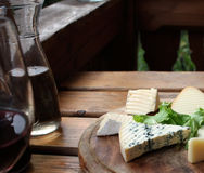 Rustic Cheese and Wine. Various slices of cheese on a traditional round wooden plate with wine on the side Stock Photo
