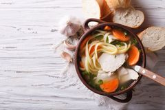 Rustic chicken soup with noodles. Horizontal top view Stock Image