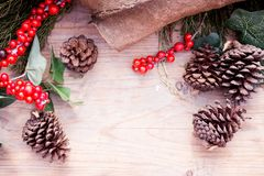 Rustic christmas background: cypress branch, fir-cone and red berries on old wooden table. Chalet, country style. New year Stock Photos