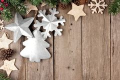 Rustic Christmas corner border with branches, wood and metal ornaments over aged wood Stock Image