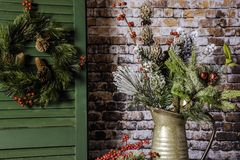 Rustic Christmas Decoration. Christmas wreath on green shutter next to winter arrangement of pine and berries with gold and red bells in metal pitcher with brick Stock Photo