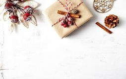 Rustic Christmas gift box with Christmas decorations on white wooden background. Flatlay. Copy space stock photography