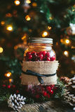 Rustic Christmas Mason Jar Decor. A rustic Christmas glass mason jar filled with cranberries and wrapped in burlap with pinecones on a wooden table and a Stock Image