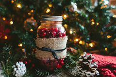 Rustic Christmas Mason Jar Decor. A rustic Christmas glass mason jar filled with cranberries and wrapped in burlap with pinecones on a wooden table and a Royalty Free Stock Photography